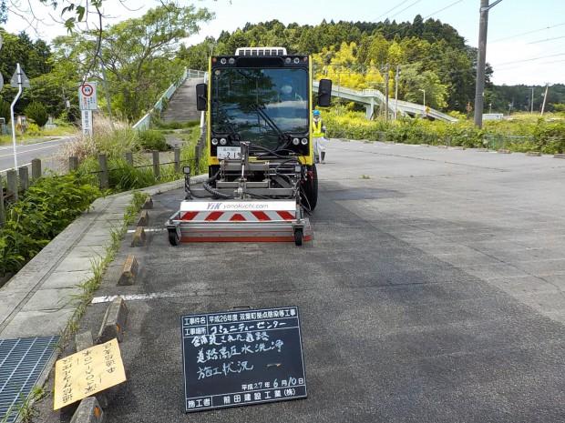 高圧水洗浄車を使用してコミュニティセンター内の駐車場を除染しています。