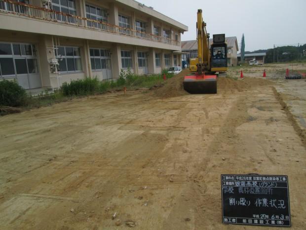 グラウンドの表土を削り取っています。