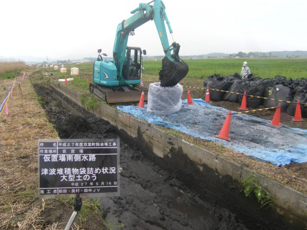 仮置場脇の用水路にたまっている堆積物を除去しています。